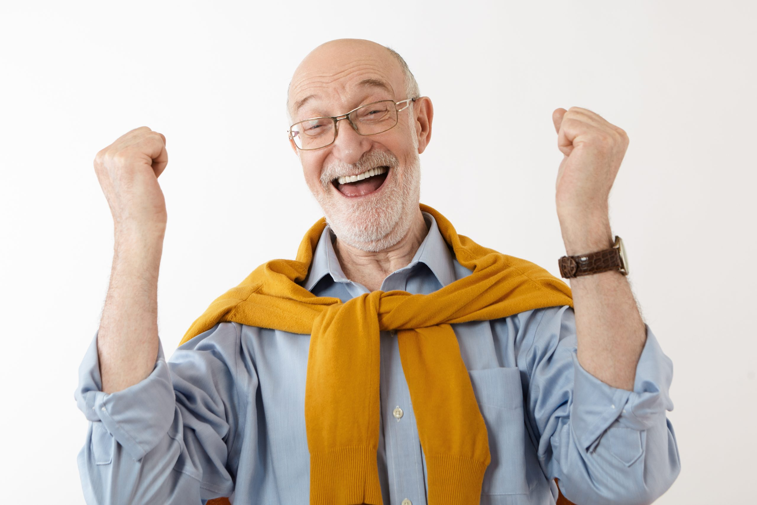 Picture of happy mature man feeling overjoyed and excited after he won in lottery, exclaiming cheerfully, clenching fists. People, luck, success, excitement, winning, victory and good fortune